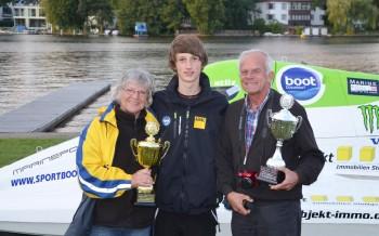 Max Stilz mit den Besuchern, Pokalen und dem Motorboot dahinter.