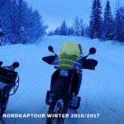 Zwei Motorräder auf einer verschneiten Straße im Dämmerlicht