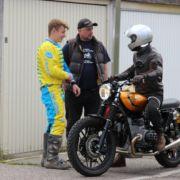 Drei Personen unterhalten sich eine sitzt auf dem Motorrad